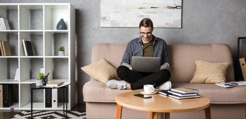 homem sentado no sofá da sala com um notebook no colo